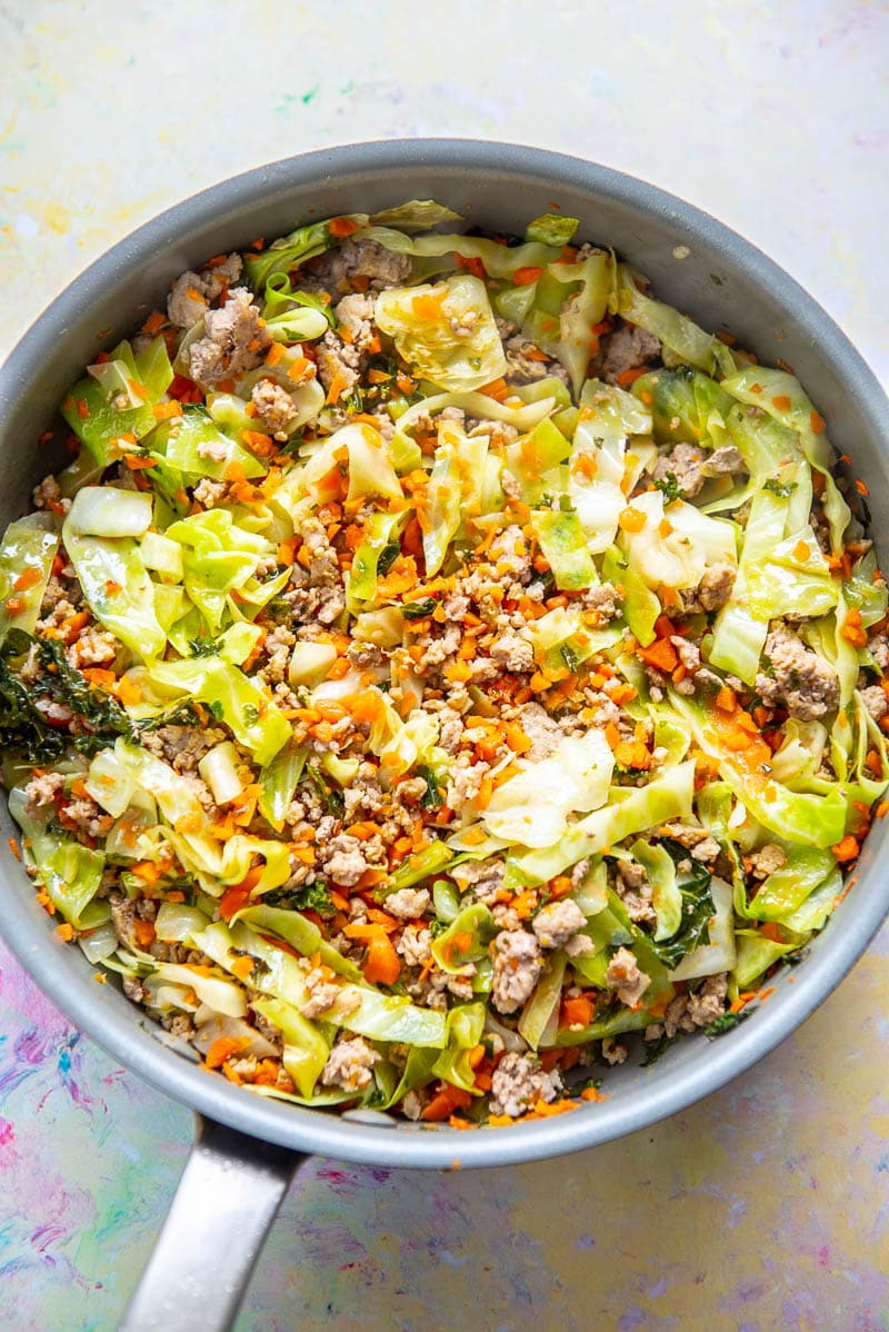 tall sided skillet filled with ground pork and chopped cabbage
