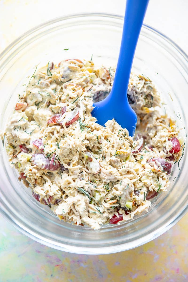 glass bowl filled with shredded chicken salad and blue spatula
