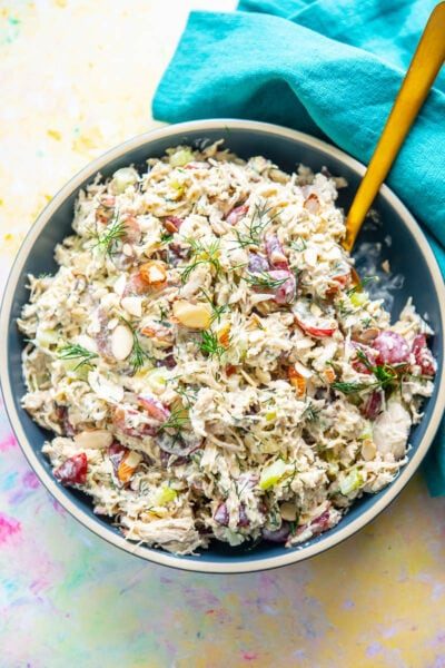blue bowl filled with shredded chicken salad filled with grapes