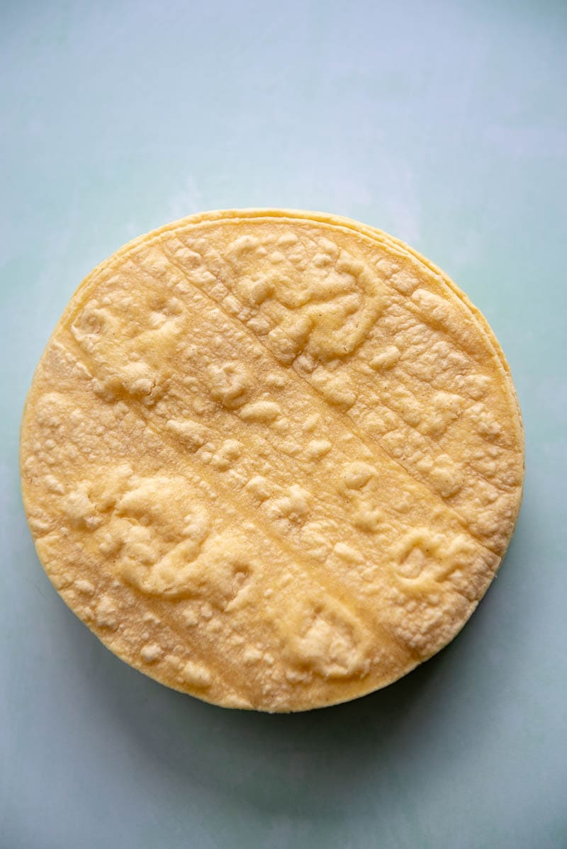 stack of corn tortillas on blue background