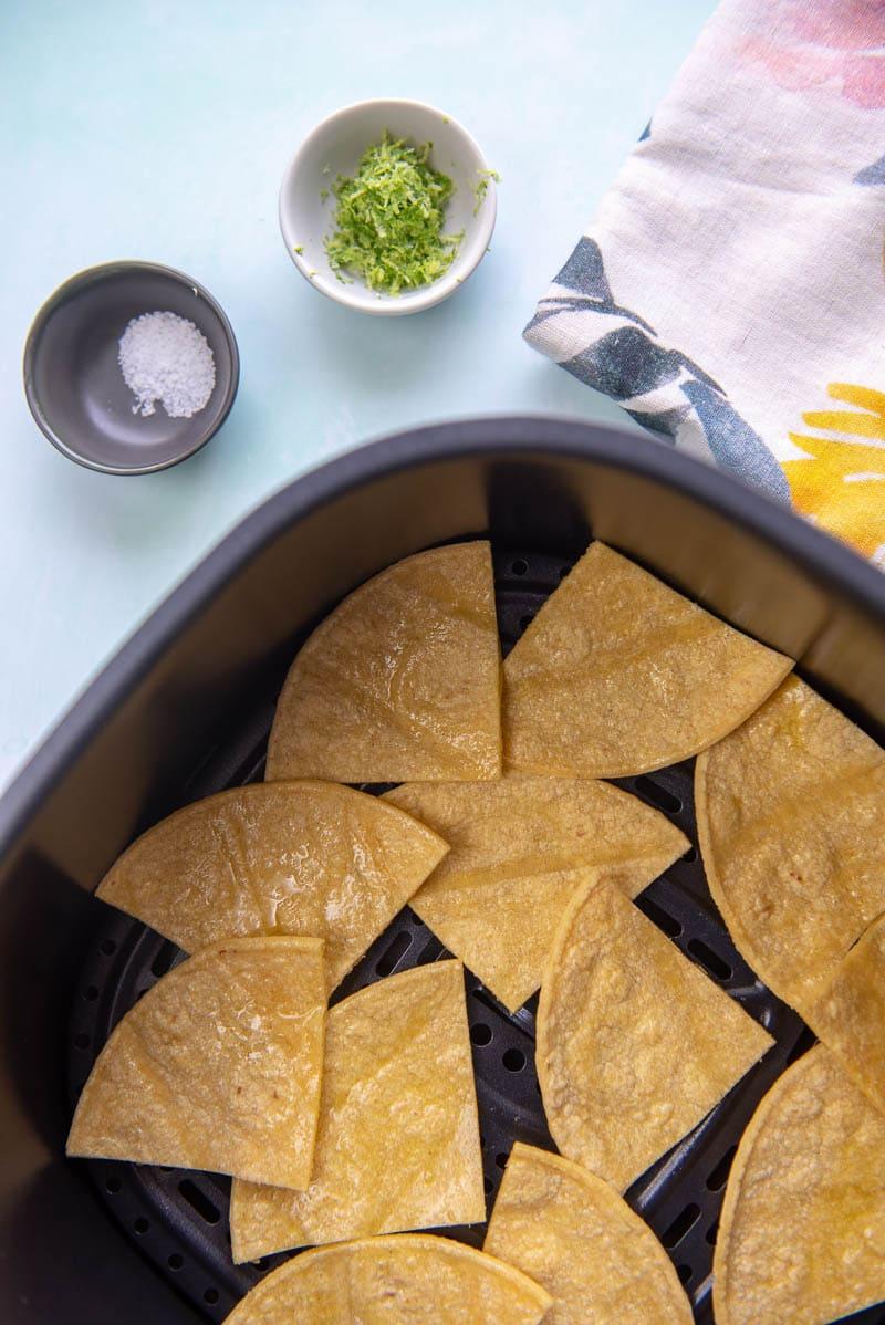 corn tortillas in air fryer basket next to bowls of salt and lime zest