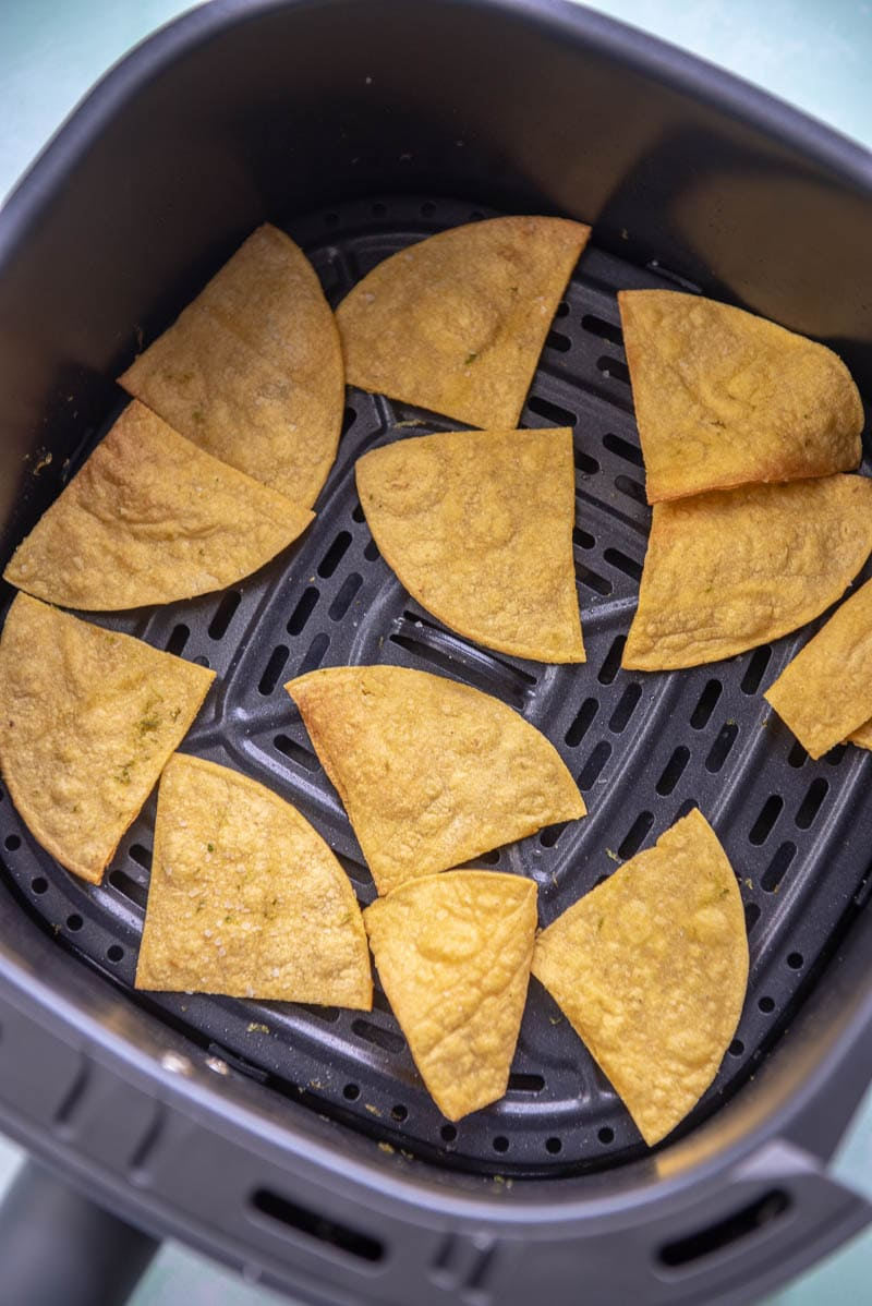 air fryer basket with just cooked corn tortilla chips