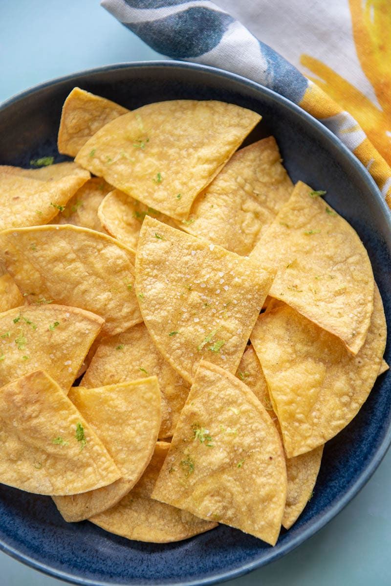 close up of tortilla chips on a blue plate topped with lime zest