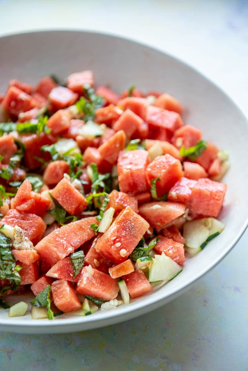 side view of white bowl filled with watermelon salad with cucumber and basil