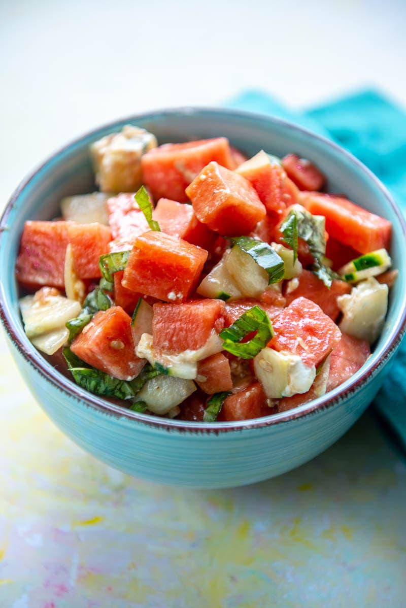 blue bowl filled with watermelon and basil salad
